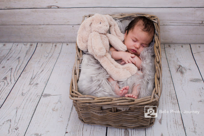 new born baby in basket prop with rabbit toy