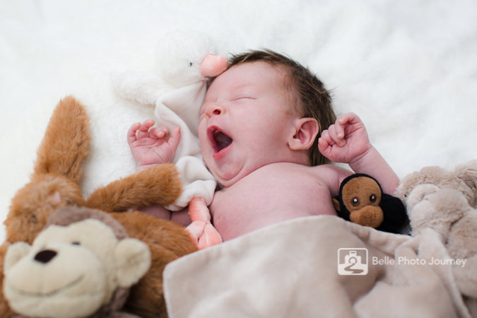 yawning baby in bed surrounded by toys