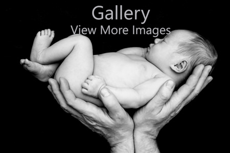 Newborn baby in fathers hands - crouch end photographer