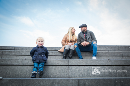 Family lifestyle photo - boy and parents sit on steps at Tower Bridge, London