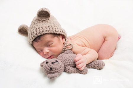 Newborn baby cuddling teddy bear by crouch end photographer