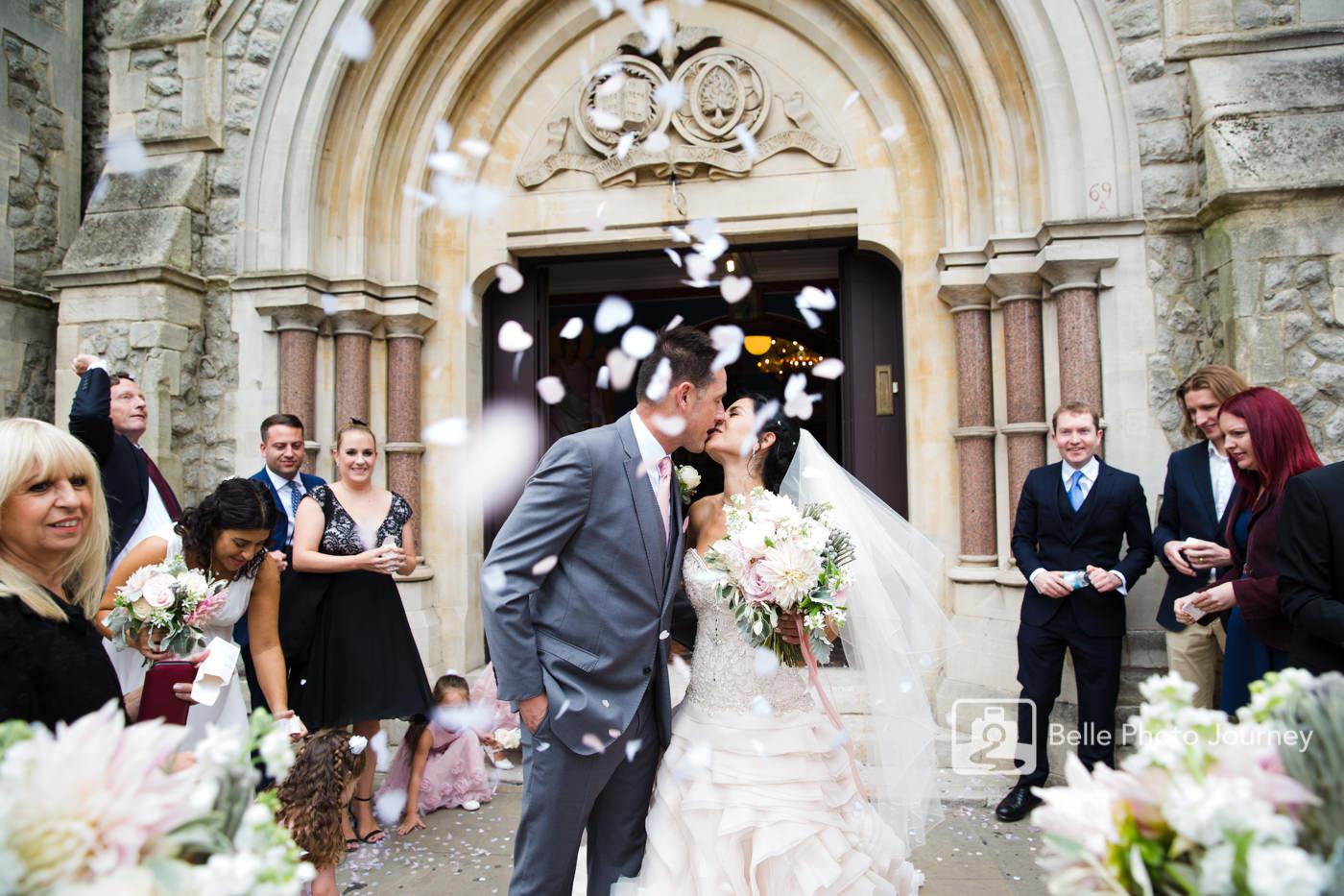confetti outside greek orthodox church bride groom couple kissing