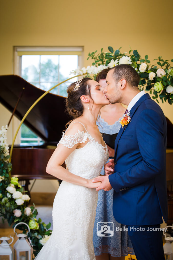 couple kissing at altar flower gold arc piano