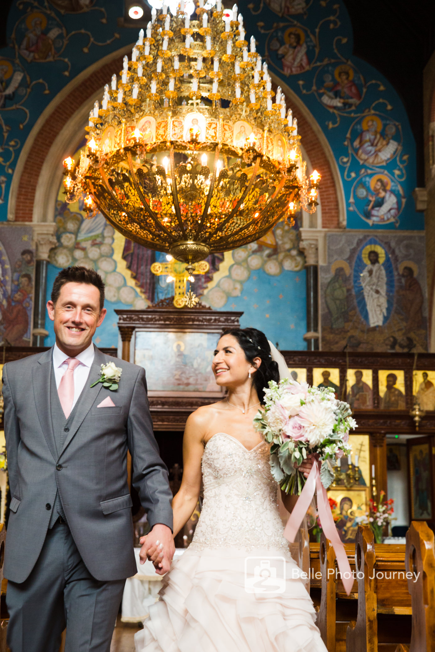 couple marching out of greek orthodox blue church chandellier croydon