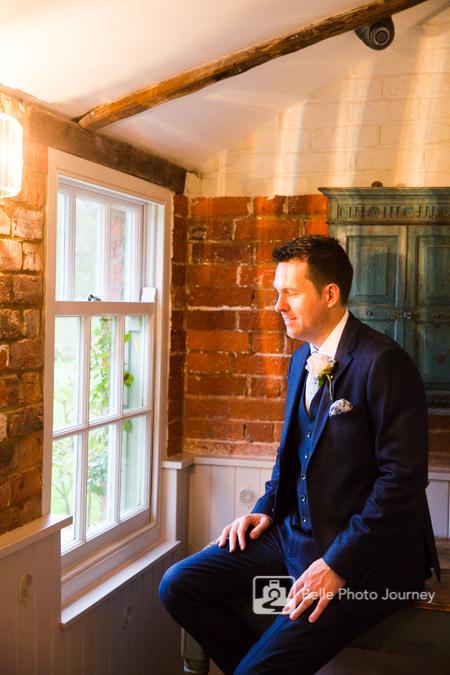 groom moody portrait look out at window in shadow sopley mill